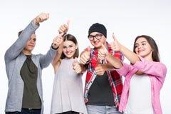 Groupe heureux d'amis avec des pouces d'isolement au-dessus d'un fond blanc Photographie stock libre de droits