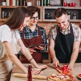 Groupe heureux d'amis faisant cuire ensemble dans la cuisine Cuisson des clas Photo stock