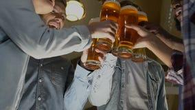 Groupe heureux d'amis faisant tinter les verres de bière, célébration de fête d'anniversaire dans le bar clips vidéos
