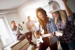 Groupe heureux d'amis jouant des instruments et faire la fête Image stock