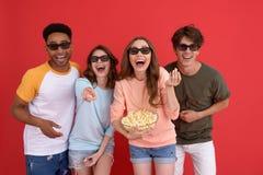Groupe heureux d'amis observant le film mangeant du maïs éclaté Photographie stock libre de droits