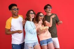 Groupe heureux d'amis observant le film mangeant du maïs éclaté Image libre de droits