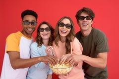 Groupe heureux d'amis observant le film mangeant du maïs éclaté Images stock