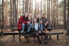 Groupe heureux d'amis s'asseyant dehors dans la forêt Photographie stock libre de droits