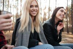 Groupe heureux d'amis s'asseyant dehors dans la forêt Images stock