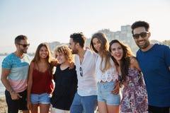 Groupe heureux d'amis se tenant ensemble dans la rangée dehors Image stock