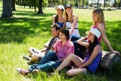 Groupe heureux d'amis souriant à l'extérieur Photos stock