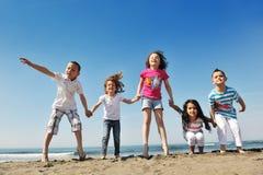 Groupe heureux d'enfant jouant sur la plage Photographie stock