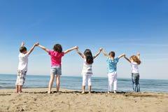 Groupe heureux d'enfant jouant sur la plage Image libre de droits