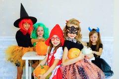 Groupe heureux d'enfants dans des costumes pendant la partie de Halloween Photos stock