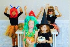 Groupe heureux d'enfants dans des costumes pendant la partie de Halloween Photographie stock