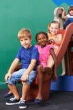 Groupe heureux d'enfants jouant sur la glissière Photos stock
