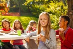 Groupe heureux d'enfants s'asseyant à la table en bois Photos stock