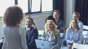 Groupe heureux de gens d'affaires écoutant parler de séminaire de Leading Presentation At de femme d'affaires banque de vidéos