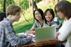 Groupe heureux de jeunes étudiants s'asseyant et étudiant Image libre de droits
