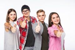 Groupe heureux de jeunes amis donnant des pouces jusqu'à l'appareil-photo sur le fond blanc Image libre de droits