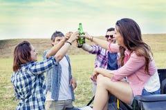 Groupe heureux de jeunes amis grillant avec de la bière Image stock