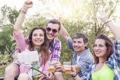 Groupe heureux de jeunes amis grillant avec de la bière Image libre de droits