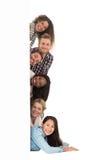 Groupe heureux de jeunes amis jetant un coup d'oeil par derrière un mur Images stock