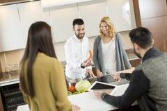 Groupe heureux de jeunes hommes et de femmes dans la cuisine moderne Photos stock