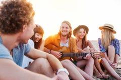 Groupe heureux de l'ami ayant la partie sur la plage Photo libre de droits