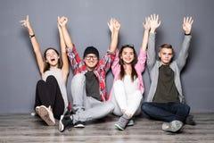 Groupe heureux de sourire d'amis et d'heureux augmenté de mains sortis Photos stock