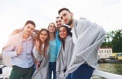 Groupe heureux de sourire d'amis posant pour l'appareil-photo dehors sur le pilier de plage Photo stock