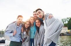 Groupe heureux de sourire d'amis posant pour l'appareil-photo dehors sur le pilier de plage Images stock