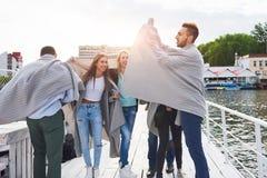 Groupe heureux de sourire d'amis posant pour l'appareil-photo dehors sur le pilier de plage Photos stock