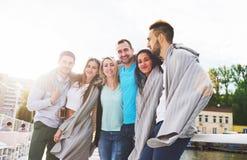 Groupe heureux de sourire d'amis posant pour l'appareil-photo dehors sur le pilier de plage Image libre de droits