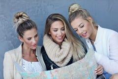 Groupe heureux de touristes s'asseyant dehors avec la carte dans la saison d'automne Photo libre de droits