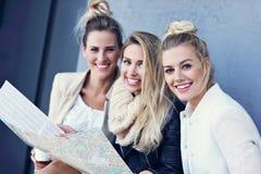 Groupe heureux de touristes s'asseyant dehors avec la carte dans la saison d'automne Image stock