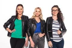 Groupe heureux de trois femmes posant dans le studio Images libres de droits