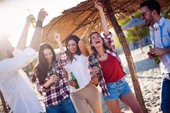 Groupe heureux des jeunes ayant l'amusement sur la plage Photo stock