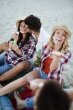 Groupe heureux des jeunes ayant l'amusement sur la plage Photographie stock