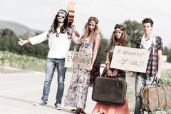 Groupe hippie faisant de l'auto-stop sur une route de campagne Photos stock