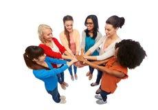 Groupe international de femmes avec des mains ensemble Photo stock