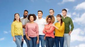 Groupe international de personnes heureuses au-dessus de ciel bleu Photos stock