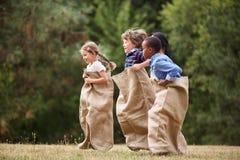 Groupe interracial d'enfants à la course de sac images stock