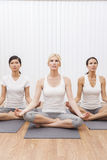 Groupe interracial de femmes en position de yoga Image stock