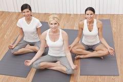 Groupe interracial de la belle position de yoga de femmes Photographie stock