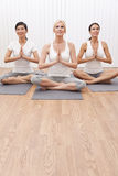 Groupe interracial de trois femmes en position de yoga Photo stock