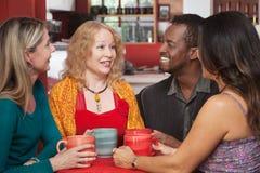 Groupe joyeux de quatre en café Images stock