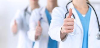 Groupe of medicine doctors show OK sign with thumb up close up. Success and high level service in health care, best. Treatment and customer loyalty and physical royalty free stock photo