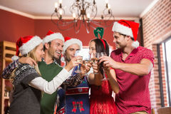 Groupe mignon d'amis grillant avec des chapeaux de Santa Photos stock