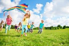 Groupe mignon d'enfants courus avec le cerf-volant Image stock