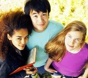 Groupe mignon de teenages au bâtiment de l'université avec des huggings de livres, nations de diversité Photographie stock libre de droits