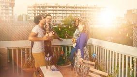 Groupe millenial multi-ethnique d'amis faisant la fête et appréciant une bière sur le terrasse de dessus de toit au coucher du so Image stock
