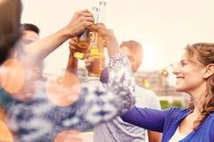 Groupe millenial multi-ethnique d'amis faisant la fête et appréciant une bière sur le terrasse de dessus de toit au coucher du so Photo stock