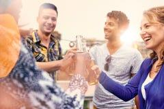 Groupe millenial multi-ethnique d'amis faisant la fête et appréciant une bière sur le terrasse de dessus de toit au coucher du so Photos libres de droits